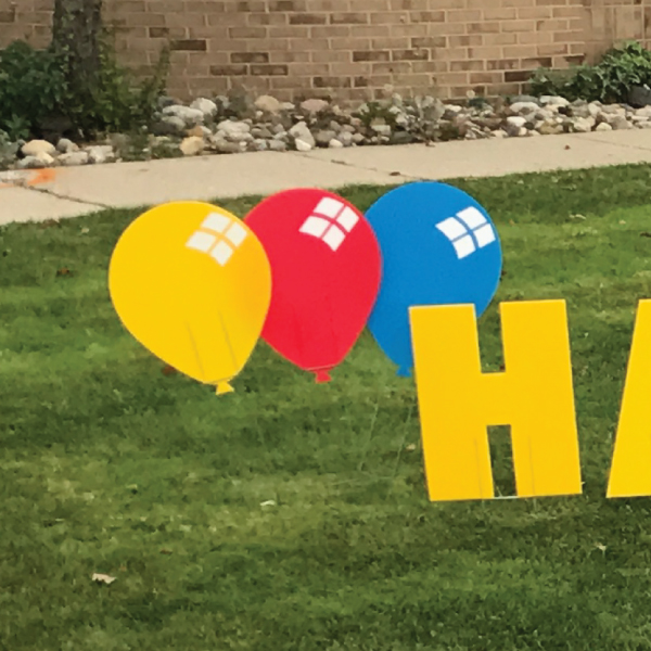 balloons_yellow_red_blue_yard_greetings_cards_lawn_signs_happy_birthday_over_hill